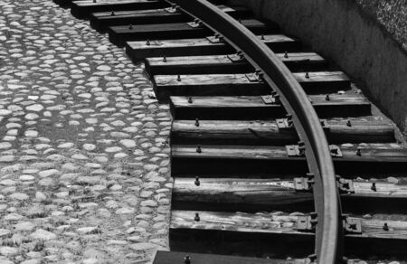 Grungy turning rail on dark wooden sleepers, vintage reversal circle for steam locomotives, black and white photo