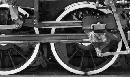 Wheels of a steam locomotive with power parts, front view, black and white photo Standard-Bild