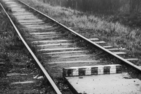 Empty railway and striped wooden border sign, background black and white photo
