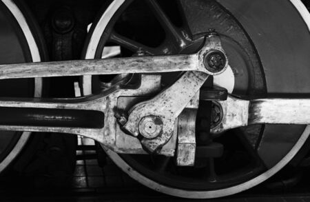 Wheel of vintage steam locomotive with connecting rod, close-up black and white photo Standard-Bild