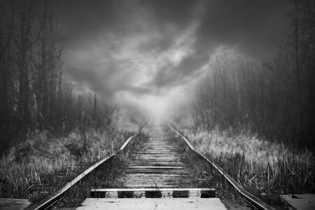 Empty railway perspective and striped wooden border sign are under dramatic stormy sky, background black and white photo Standard-Bild