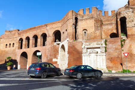 Rome, Italy - February 13, 2016: Rome street view with parked cars near old fortification walls of Porta Pinciana, it is a gate of the Aurelian Walls in Rome Editorial