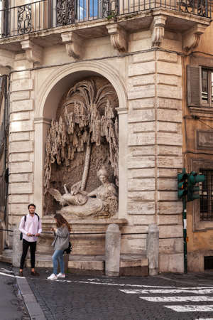 Rome, Italy - February 13, 2016: Rome vertical street view with tourists near ancient street sculpture Editorial
