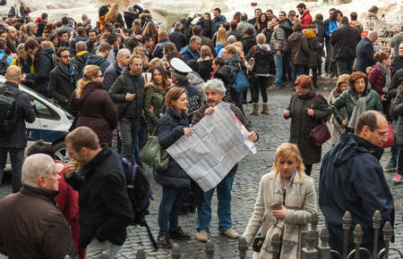 Rome, Italy - February 13, 2016: Tourists are near the Trevi Fountain an iconic symbol of Imperial Rome. It is one of the most popular tourist attractions in Rome Editorial
