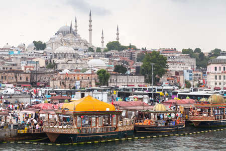 Istanbul, Turkey - June 28, 2016: Istanbul city view, Eminonu former district. People are on the coast of Golden Horn, Suleymaniye Mosque is on a background