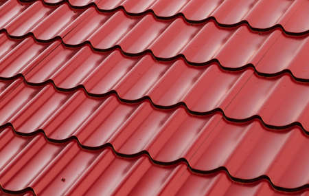 Red metal shingles roof slope, background photo texture