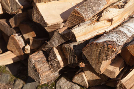 Pile of firewood, birch chocks lay stacked, outdoor photo