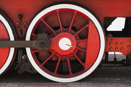 Red white wheel of vintage steam locomotive with connecting rod, close-up photo, front view