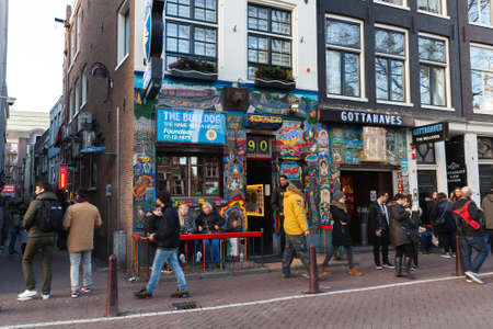 Amsterdam, Netherlands - February 24, 2017: Street view of old Amsterdam with people walking near coffeeshop Bulldog