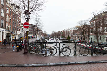 Amsterdam, Netherlands - February 25, 2017: Bicycles are parked on the bridge in old Amsterdam