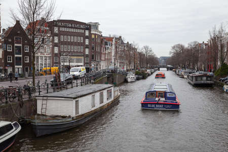 Amsterdam, Netherlands - February 25, 2017: Tourist boat with tourists goes at the canal of Amsterdam city