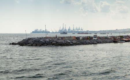 Istanbul, Turkey - June 30, 2016: People are on the breakwater in Avcilar port