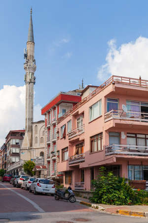 Istanbul, Turkey - June 30, 2016: Narrow street in Istanbul with mosque, cars are parked on the roadside, vertical photo