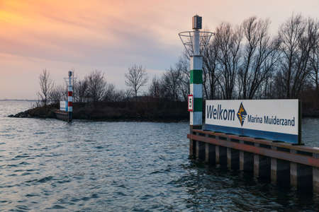 Amsterdam, Netherlands - February 21, 2017: Entrance pier with lighthouse in marina Muiderzand