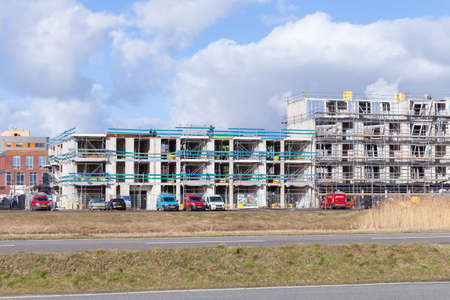 Amsterdam, Netherlands - February 24, 2017: Modern living houses are under construction under blue cloudy sky