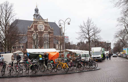 Amsterdam, Netherlands - February 25, 2017: Marketplace Noordermarkt view with parked bicycles and walking people