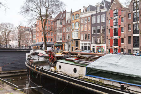 Amsterdam, Netherlands - February 25, 2017: Traditional old living houses and boats are at the canal in Amsterdam