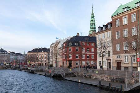 Copenhagen, Denmark - December 9, 2017: Ved Stranden street view with Nikolaj Copenhagen Contemporary Art Center on a background. Ordinary people walk the street