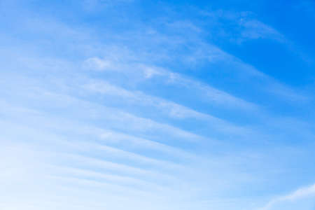 Stripes of windy clouds in the blue sky at daytime, natural photo background texture