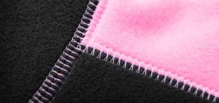 Black pink fleece jacket seams, close up photo