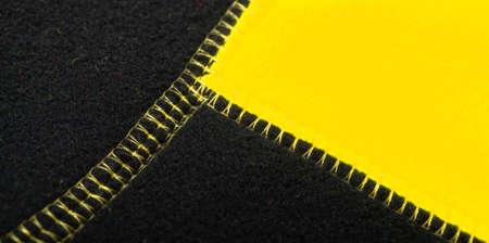 Yellow black fleece jacket seams, close up photo