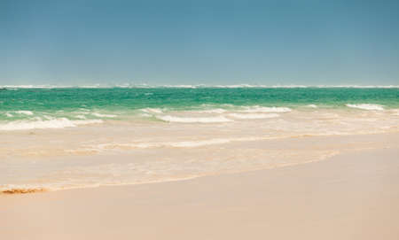 Empty coastal Caribbean landscape with sandy coast and waves. Atlantic ocean coast, Dominican republic. Bavaro beach. Background photo