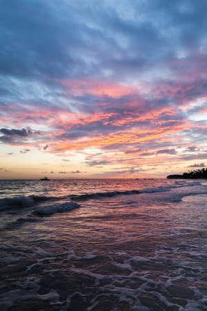 Colorful sunrise sky over Atlantic Ocean coast. Bavaro beach. Dominican Republic, vertical coastal landscape