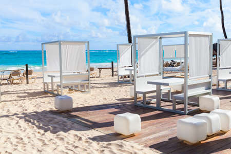 Empty sun loungers and gazebos are on sandy beach at sunny day, Dominican Republic