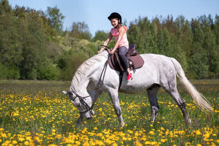Girl is on a white horse breed Orlov trotter at sunny day