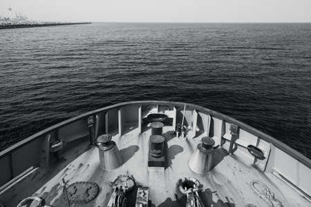 Bow of a tug boat and seawater. Blue toned monochrome photo taken from a captains bridge