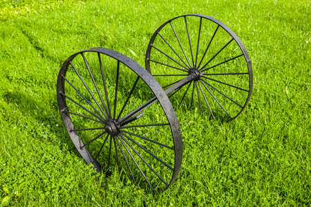 Black vintage metal wheels on one axis standing on green grass at sunny summer day