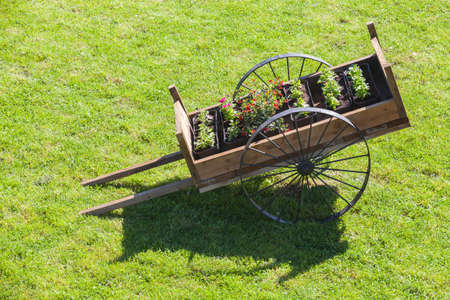 Vintage wooden cart with flower pots stands on green grass at summer day Banco de Imagens