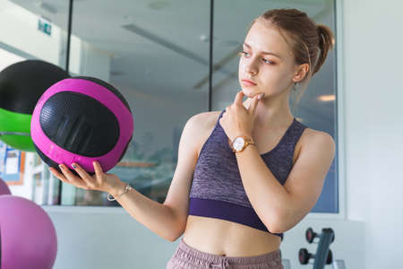 Young beautiful blond sporty girl in a gym holds black pink med ball