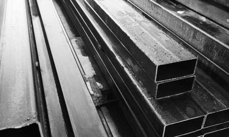 Stack of rolled metal products, gray steel pipes with rectangular cross-section, close-up black and white photo with selective soft focus