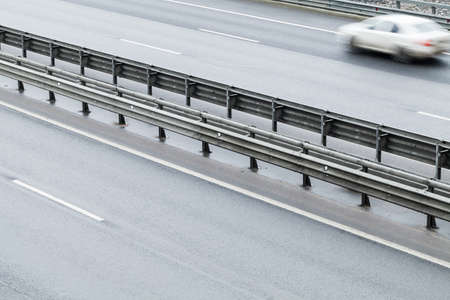 Fast blurred car is on a highway with dividing structure, abstract transportation photo Stock Photo