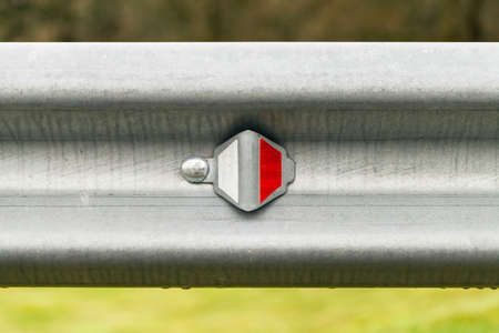 Retro-reflecting optical unit is on a metal guardrail. Highway safety equipment, close-up