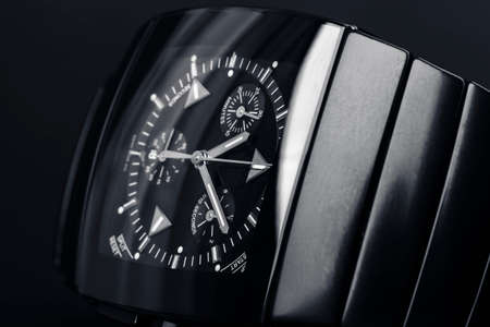 Luxury modern wrist watch with square body made of black ceramics. Close-up photo with selective soft focus