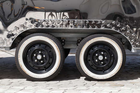 Wheels of shiny vintage trailer for fast food delivery standing on cobbled road