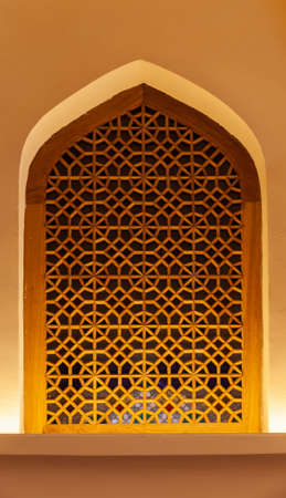 Ancient window with Arabic geometric pattern, colorful glass in wooden frame