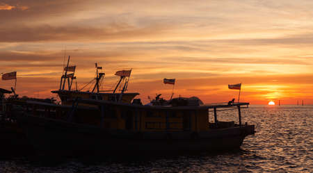 Silhouettes of fishing boats with flags moored near KK Fish Market at sunset
