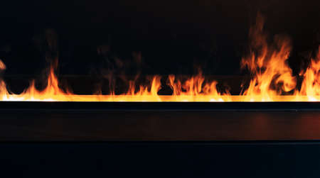 Burning fire over dark background, modern open fireplace close-up photo