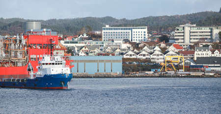 Bergen port view on a daytime, industrial ships are moored in harbor. Norway