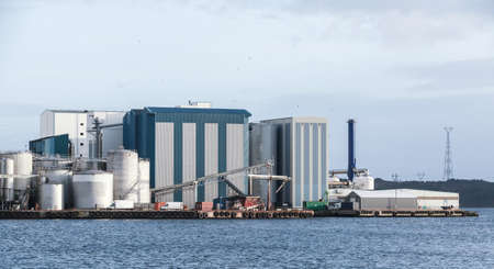 Norwegian fish factory, industrial buildings and tanks stand on a seacoast. Bergen, Norway