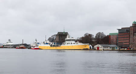Fish Carrier ship with yellow hull is moored in Bergen Port, Norway