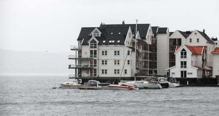 Bergen, Norway. Coastal view with living houses and boats on a cloudy day