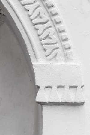 Vertical architectural background with an arch in a white wall. Ancient Russian temple facade decoration