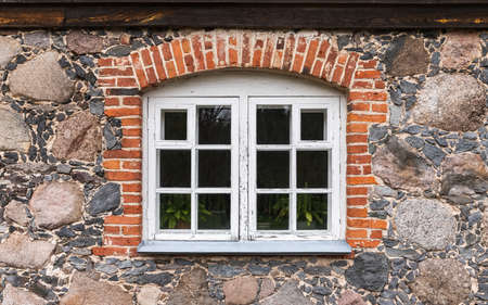 Window with white wooden frame in a stone wall with brick arch