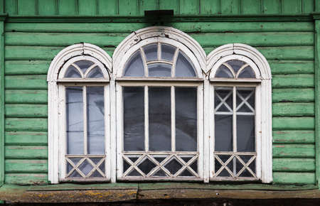 Triple arched window with white wooden frame in grungy green wooden wall, Russian rural architecture background photo fragment