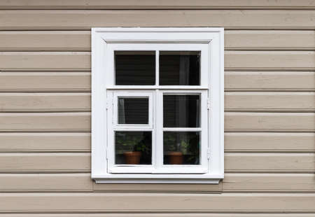Window with white wooden frame in a beige painted wall