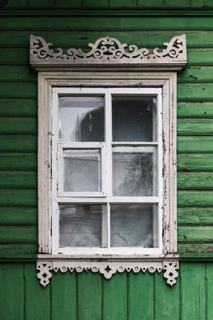 Window in white decorative frame in an old rural wooden house wall, architectural background texture 版權商用圖片